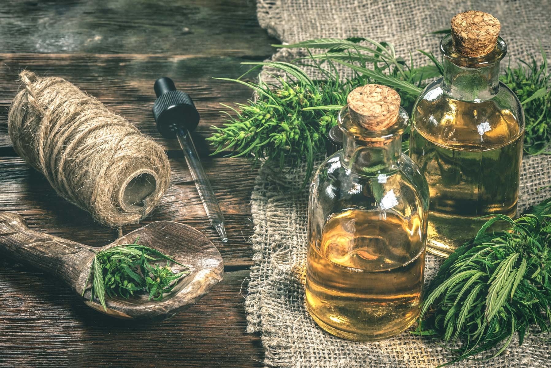 CBD oil bottles and green plant of cannabis on a wooden backgrou